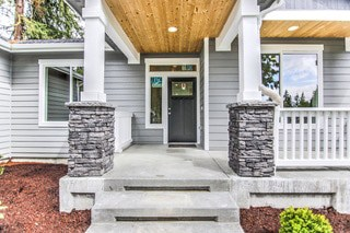 Steps leading up to the front door with a covered patio over it | Reality Homes