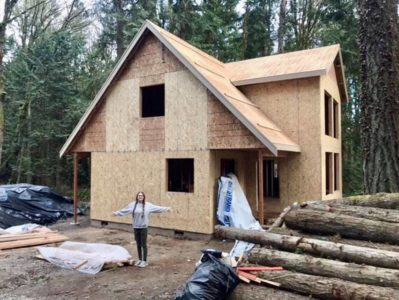 Woman with her arms extended in front of a home in construction | Reality Homes